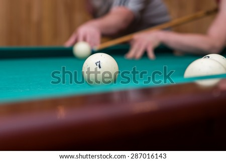 The man is going to hit on a billiard ball using the cue
