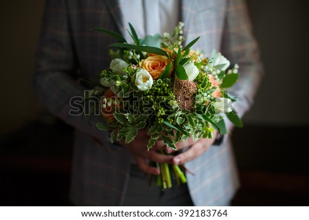 the man is holding a bouquet of flowers