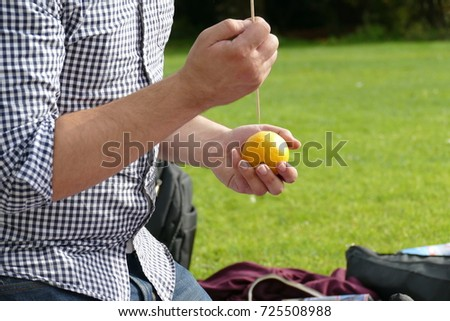 the man is holding an orange or lemon