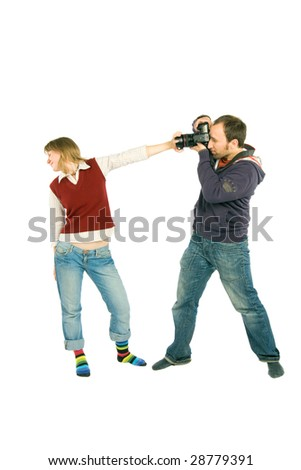 The man is shooting the young woman, but she shuts the objective with her hand. - stock photo