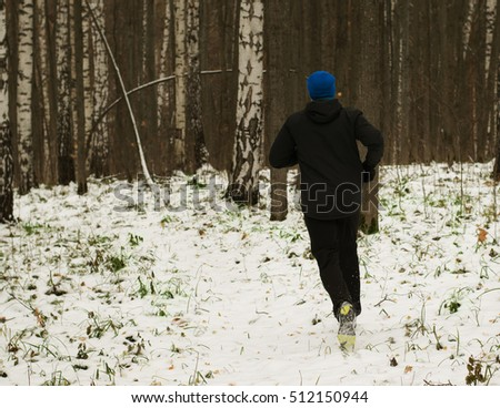 The man likes to run in the winter forest. Healthy lifestyle concept.