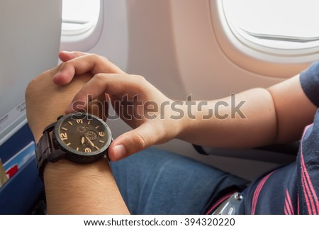 The man looking to the watch on the airplane for urgent period concept - stock photo