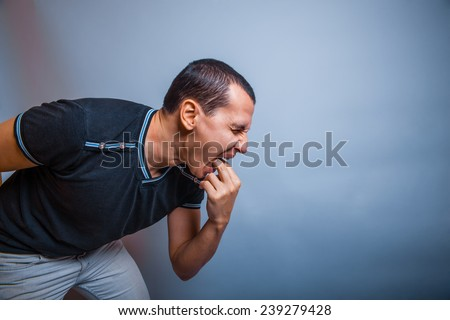 the man of European appearance brunet causes vomiting putting his fingers in his mouth on a gray background