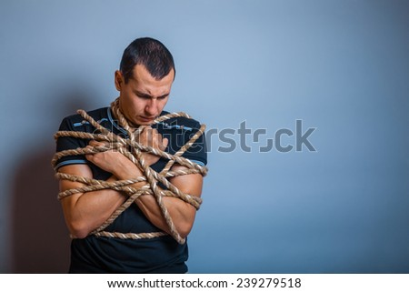 the man of European appearance brunet tied with a rope hung his head on a gray background - stock photo
