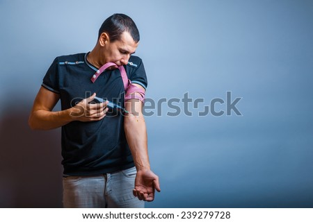 the man of European appearance brunette pulled tourniquet hand injected into a vein drug addict - stock photo