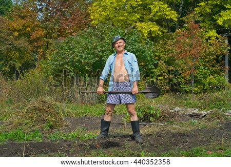 The man on garden with spade in his hands. - stock photo