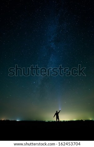 The man on the background of bright stars of the night sky. The Milky Way. - stock photo
