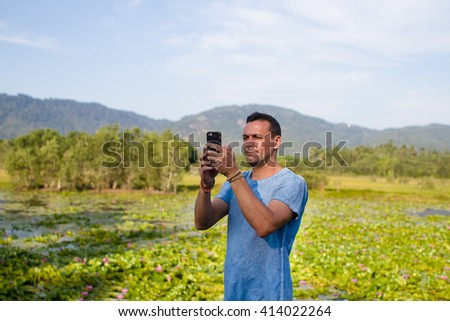 The man photographs the nature on the telehair dryer - stock photo