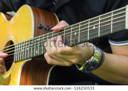 The man playing acoustic guitar
