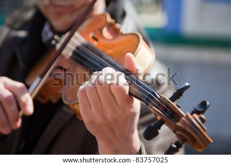 The man plays a violin. Hands of the musician close up.