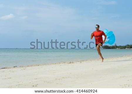 The man runs, runs on the beach, in the tropical country plays sports, with attached running a parachute behind the back - stock photo