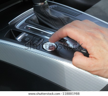 the man's hand presses the car engine ignition button