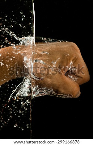 The Man's Hand Punch To the Water On Black Background - stock photo