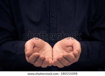 The man's hands in a gesture of holding something or ask for help - stock photo