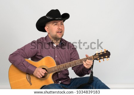 The man's portrait in a cowboy's hat. He sits in a jacket and jeans and smiles. He sits in a shirt and jeans. He plays the guitar and sings.