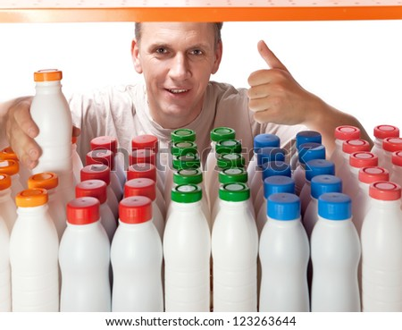 The man selects dairy products in the shop - stock photo