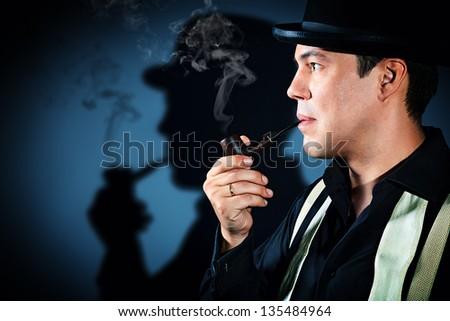 The man smoking tobacco pipe - stock photo