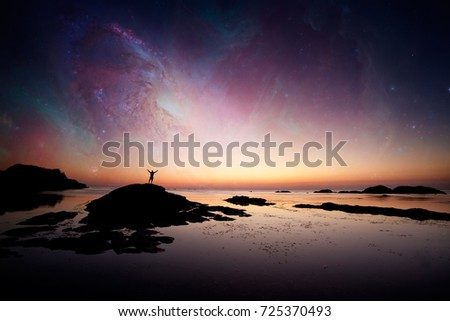 The man stand on the rocks background of the galaxy, concept for dream and universe - elements of this image are furnished by NASA