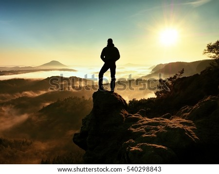 The man standing high on cliff. Hiker climbed up to rocky peak and enjoy view to valley bellow. Man  watch over misty and foggy morning valley in morning Sun.