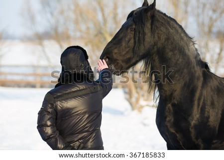 The man strokes the horse's head in winter