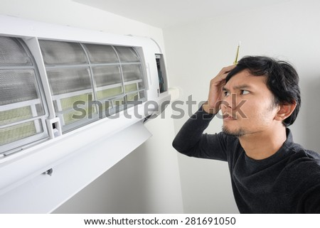 the man trying to fix air condition by himself - stock photo