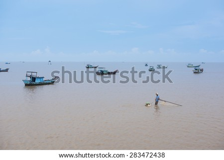 The man use fishing net to catch fish in the beach beside fishing boat - stock photo