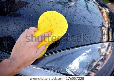 the man using yellow sponge to wash his car - stock photo