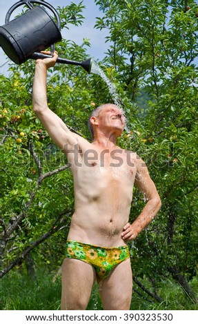 The man waters himself from a watering can in orchard. - stock photo