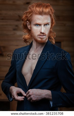 The man wears a jacket over his naked body, his fiery red hair. - stock photo