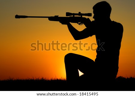 The man who shoots from a sniper rifle against a sunset.