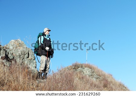 The man with a backpack standing on mountain top in the fall
