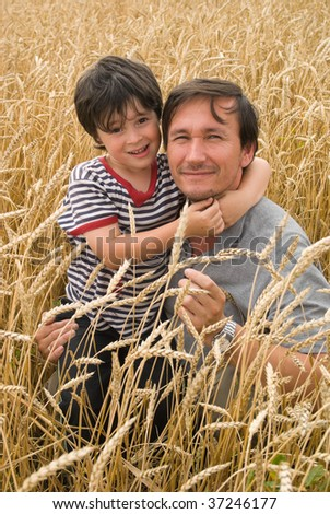 The man with boy on field of cereal - stock photo