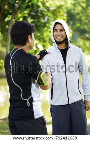 The man with friend greeting in the park when  exercise in the morning time . Two Asian athletic friends greeting each other with arm wrestling in the park , friendship concept