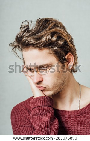 The man with glasses tired sleepy. On a gray background. - stock photo