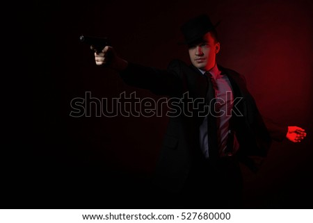 the man with the gun, wearing a black hat, suit