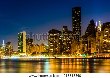 The Manhattan Skyline and the East River at night, seen from Roosevelt Island, New York.