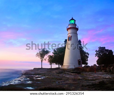 The Marblehead Lighthouse Radiates It's Green Light As The Sun Warms The Eastern Sky Initiating A Brand New Day At Marblehead Ohio On Lake Erie, USA - stock photo