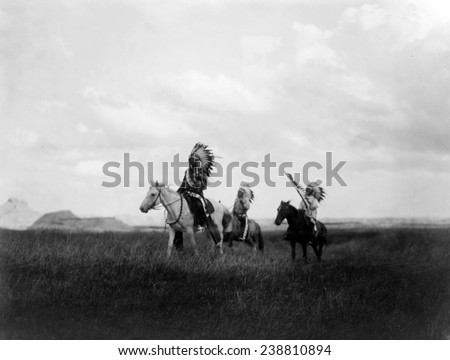 The March of the Sioux, three Sioux Indians on horseback on plains with rock formations in background, photograph by Edward S. Curtis, 1905 - stock photo