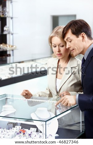 The married couple chooses a jeweller ornament - stock photo