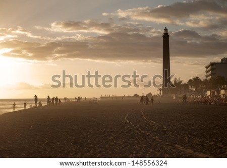 The Maspalomas beach at dusk with reddish tones. People are leaving the beach at sunset - stock photo