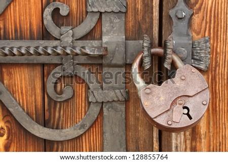 The massive iron lock on wooden gate/Old padlock on a wooden door - stock photo
