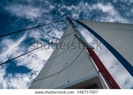 The mast and sails recreational catamaran on a background of cloudy sky