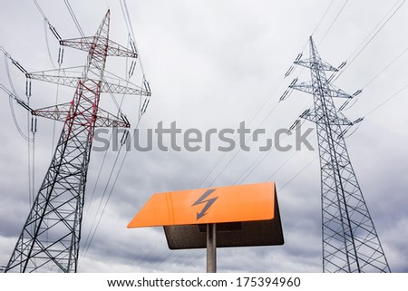 the mast of a high voltage transmission line for electricity before dark clouds. - stock photo