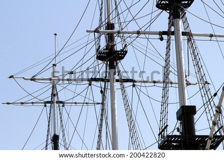 The mast of a sailing ship against a blue sky background - stock photo