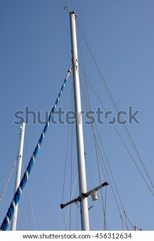 The mast of the ship with the rigging against a blue sky