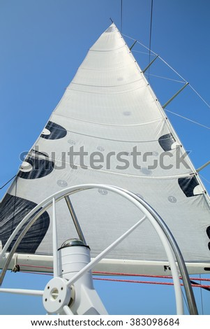 The mast, sail and rudder of the yacht on the background of blue sky - stock photo