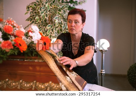 The master of funeral ceremonies prepares a coffin and flowers for burial in a ceremony hall - stock photo
