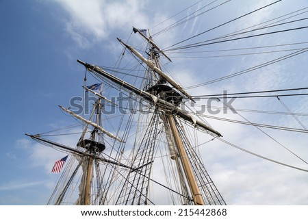 The masts and rigging of the tall ship U.S. Brig Niagara against a blue, cloud filled sky. - stock photo