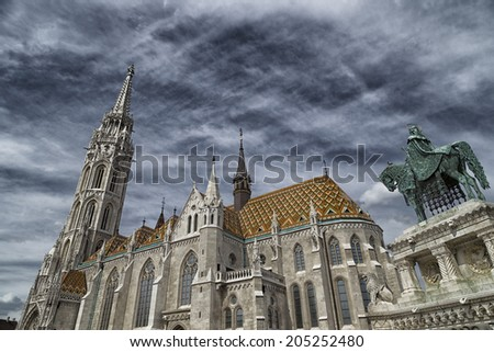 The Mathias Church in Budapest (Hungary) or Church of Our Lady: red and orange diamond patterned roof tiles, neo-Gothic rose window and white towers on dark dramatic cloudy sky. Statue of St. Stephen - stock photo