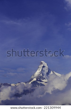 The Matterhorn Mountain in the Swiss Alps. Two paragliders are seen, tiny, in the lower foreground against the clouds. - stock photo